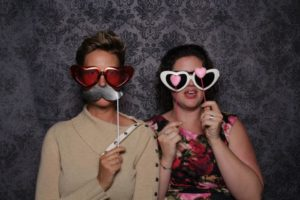 Jennifer (Left) and Kate (Right) in a prop Photo Booth. Jennifer is wearing a cream colored sweater with asymmetrical collar, heart shaped red sunglasses, and holding up a black paper mustache on a stick. Kate is wearing a floral dress, wearing white heart shaped sunglasses, and holding up two pink hearts on sticks; one in front of each eye.